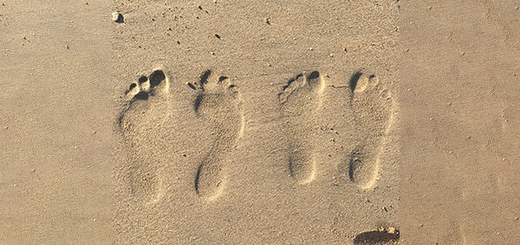 His Her foot prints in sand