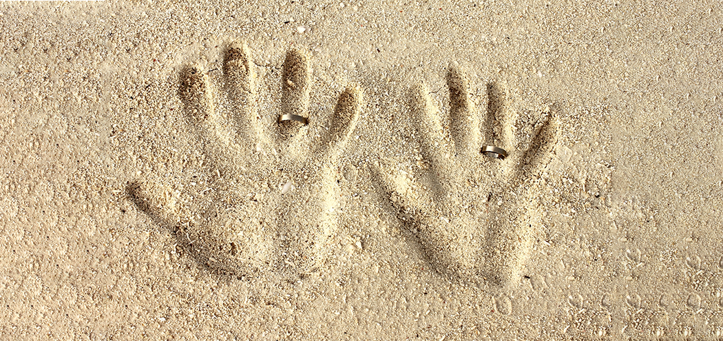 His her hand prints in sand